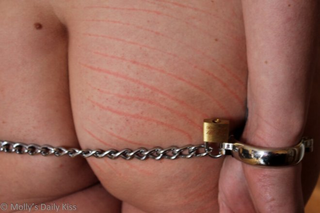 Wrists chained behind bottom with knife marks