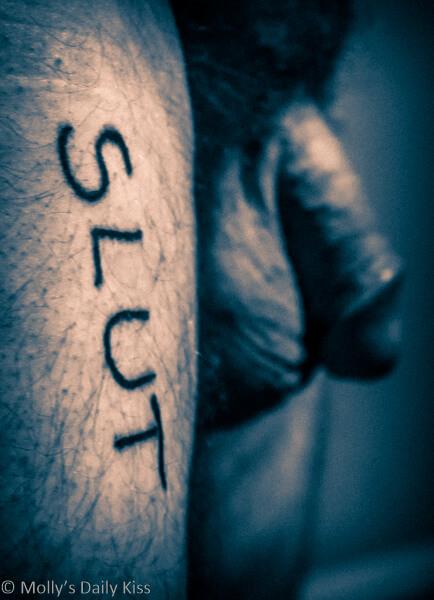 Word slut written on my thigh